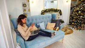 Caring wife chooses gift online on laptop for family and pays by plastic card, sitting on blue sofa in festively. Beautiful woman and keeper of home takes care stock video