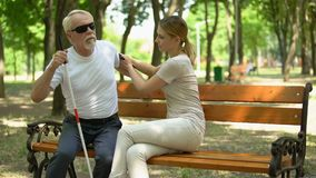 Caring woman assisting visually impaired pensioner to sit on bench, support stock video