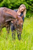 Caring woman feeding her arabian horse with snacks in the field stock photo