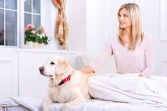Caring woman lying on bed with her dog Royalty Free Stock Photos
