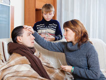 Caring woman measuring the temperature of ill husband. Caring women measuring the temperature of ill husband at home Stock Photography