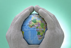 Caring World. Shot of Pottery hands holding a toy globe. The shot has been isolated using a snooted strobe to brighten the green background. No sharpening has Stock Image