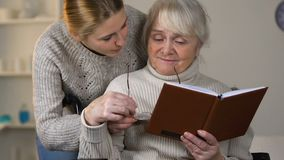 Caring young lady giving eyeglasses to aged granny reading book in wheelchair stock video footage