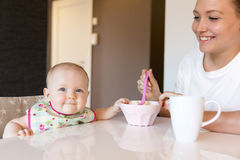 Caring young mother feeds her smiling baby girl Royalty Free Stock Photo