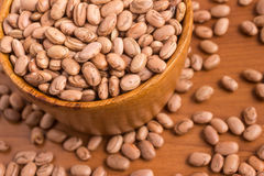 Carioca Beans into a bowl. Over a wooden table royalty free stock image