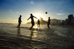 Carioca Brazilians Playing Altinho Beach Football Rio. Silhouettes of carioca Brazilians playing sunset altinho futebol beach football soccer in the waves at royalty free stock photo