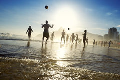 Carioca Brazilians Playing Altinho Futebol Beach Football. Silhouettes of carioca Brazilians playing sunset altinho futebol beach football soccer on the shore of royalty free stock photos