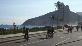 Cariocas och turister som övar nära stranden på den berömda Ipanema grannskapen i Rio de Janeiro, Brasilien - 4K lager videofilmer