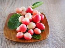 Carissacarandas of karonda zijn wit en rood met groene bladeren in houten platen Op de oude houten lijst is het een klein fruit Stock Foto's