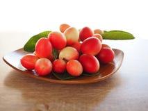 Carissacarandas of karonda zijn wit en rood met groene bladeren in houten platen Op de oude houten lijst is het een klein fruit Royalty-vrije Stock Foto's