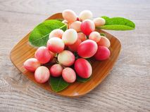 Carissacarandas of karonda zijn wit en rood met groene bladeren in houten platen Op de oude houten lijst is het een klein fruit Stock Afbeelding
