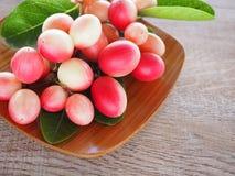 Carissacarandas of karonda zijn wit en rood met groene bladeren in houten platen Op de oude houten lijst is het een klein fruit Stock Fotografie