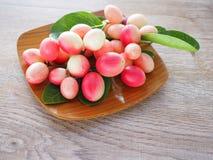 Carissacarandas of karonda zijn wit en rood met groene bladeren in houten platen Op de oude houten lijst is het een klein fruit Stock Afbeeldingen