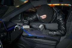 Carjacker unlock glove box with crowbar Stock Photography
