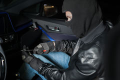 Carjacker unlock glove box with crowbar. Male thief with balaclava on his head hack car. Carjacking danger concept. Auto transport crime Stock Photography
