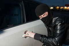 Carjacking danger, car insurance concept. Carjacking danger, car insurance advertising concept. Male thief with balaclava on his head trying to open car door Royalty Free Stock Photos