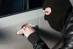 Carjacking danger, car insurance concept. Carjacking danger, car insurance advertising concept. Male thief with balaclava on his head trying to open car door Royalty Free Stock Image