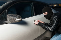 Carjacking danger, car insurance concept. Carjacking danger, car insurance advertising concept. Male thief with balaclava on his head trying to open car door Stock Photos