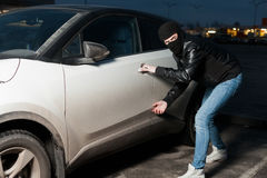 Carjacking danger, car insurance concept. Carjacking danger, car insurance advertising concept. Male thief with balaclava on his head trying to open car door Stock Photo