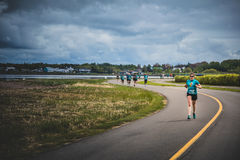 Lonely Woman Leading a Group of 10K Runners Royalty Free Stock Photos