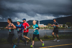 Older Woman in top Shape running with a group of Young people Stock Images