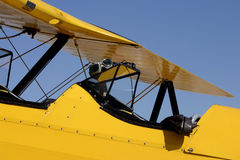 Carlinga amarilla del biplano con los anteojos del vuelo y la chaqueta de bombardero Imagen de archivo libre de regalías
