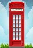 Carlingue rouge anglaise de téléphone sur l'herbe Images libres de droits
