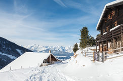 Carlingues en bois dans les Alpes autrichiens dans la neige Images stock