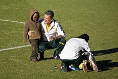 Carlos Alberto Parreira and Kid - Coaching Advise. Bafana Bafana coach Carlos Alberto Parreira invites a child spectator onto the practice pitch to view up close Royalty Free Stock Images