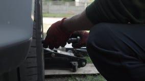 Carmakeren skruva av hjulbultarna för att ta bort hjulet av bilen arkivfilmer