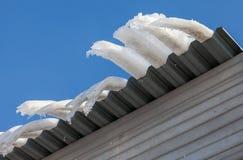 Carámbanos grandes que cuelgan en el tejado de la casa Fotos de archivo libres de regalías