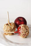 Carmel, candy and regular apple. With nuts on a white plate and white background Royalty Free Stock Photos