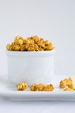 Carmel covered popcorn. In a white bowl overflowing Royalty Free Stock Images