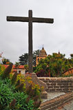 Carmel by the Sea, mission, Mission San Carlos Borromeo, catholicism, garden, flowers, California, church, architecture, cross. A wooden cross and Mission San stock photography