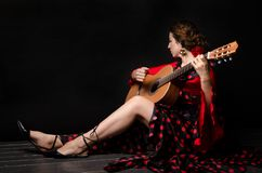 Free Carmen Beautiful Woman In Red Dress, With Guitar On Dark Background Sitting On The Floor Stock Image - 162485241