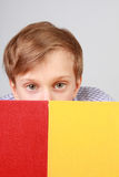 Blonder kaukasischer Junge, der von hinten zwei bunte Bücher auf Grau schaut Stockfoto