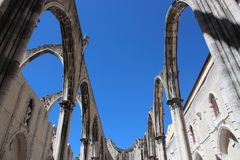 Carmo Convent Arches. Stone arches stand out against the blue sky in the ruined cathedral of Carmo Convent. Lisbon, Portugal Stock Photos