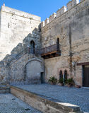Carmona castle courtyard. We see a staircase leading up their rooms, on the patio stones are round and some plants on the wall Royalty Free Stock Images