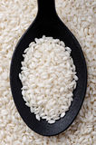 Carnaroli rice. Top view of black spoon full of carnaroli rice Royalty Free Stock Photo