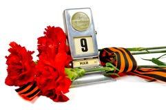 胜利在白色背景隔绝的天概念-葡萄酒金属桌面日历与5月9日日期和与红色carnat的乔治丝带 免版税库存图片