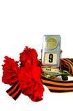 胜利在白色背景隔绝的天概念-葡萄酒金属桌面日历与5月9日日期和与红色carnat的乔治丝带 免版税图库摄影