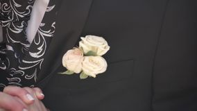 Carnation flower in a pocket. the flower in jacket pocket. pin with decorative white flowers pinned on the groom`s. Jacket. boutonniere flower in the pocket of stock video footage