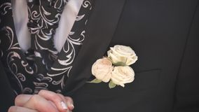 Carnation flower in a pocket. the flower in jacket pocket. pin with decorative white flowers pinned on the groom`s stock images