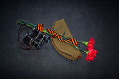 Carnation flowers, George Ribbon and military binoculars Royalty Free Stock Photos
