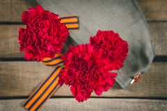 Carnation flowers, George Ribbon and military garrison cap with a red star. May 9 Victory Day Stock Photography