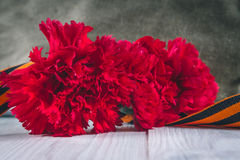 Carnation flowers, George Ribbon and military garrison cap with a red star. May 9 Victory Day Royalty Free Stock Photography
