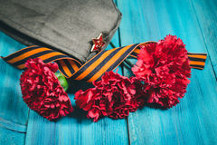 Carnation flowers, George Ribbon and military garrison cap with a red star. May 9 Victory Day Stock Image