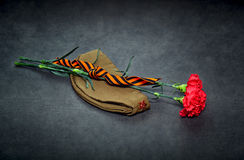 Carnation flowers, George Ribbon and military garrison cap Royalty Free Stock Photography