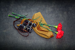 Carnation, George Ribbon, military binoculars and field cap Royalty Free Stock Photography