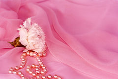 Carnation and pearls on pink silk chiffon. White flower and pearls in folds of pink silk chiffon Royalty Free Stock Images